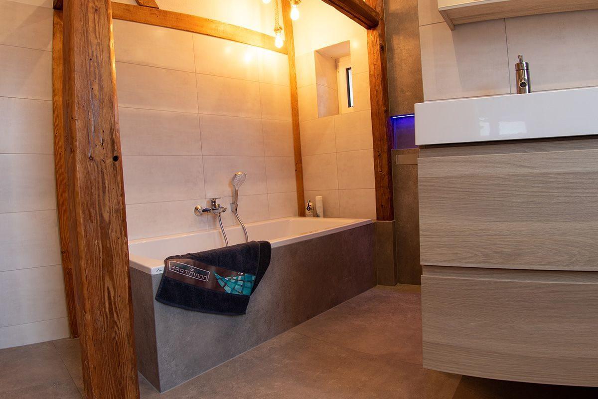 Abbildung Bad mit Bruchsteinwand und Holzbalken Blick auf Badewanne
