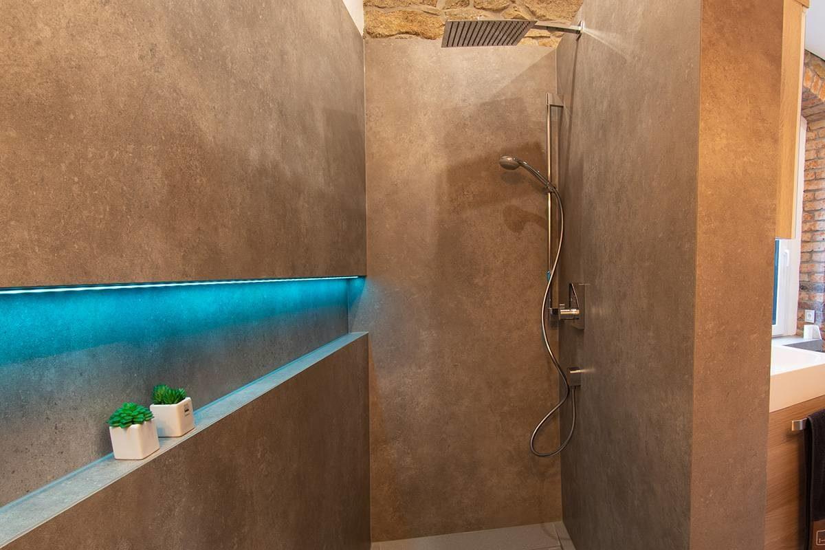 Abbildung Bad mit Bruchsteinwand und Holzbalken bodengleiche Dusche mit Regendusche und grosser beleuchteter Ablageflaeche