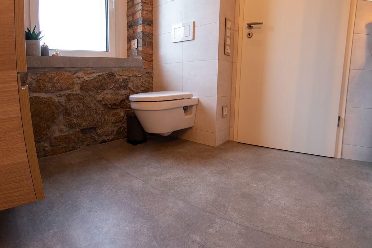 Abbildung Bad mit Bruchsteinwand und Holzbalken Blick auf Toilette, Fenster und Tuer