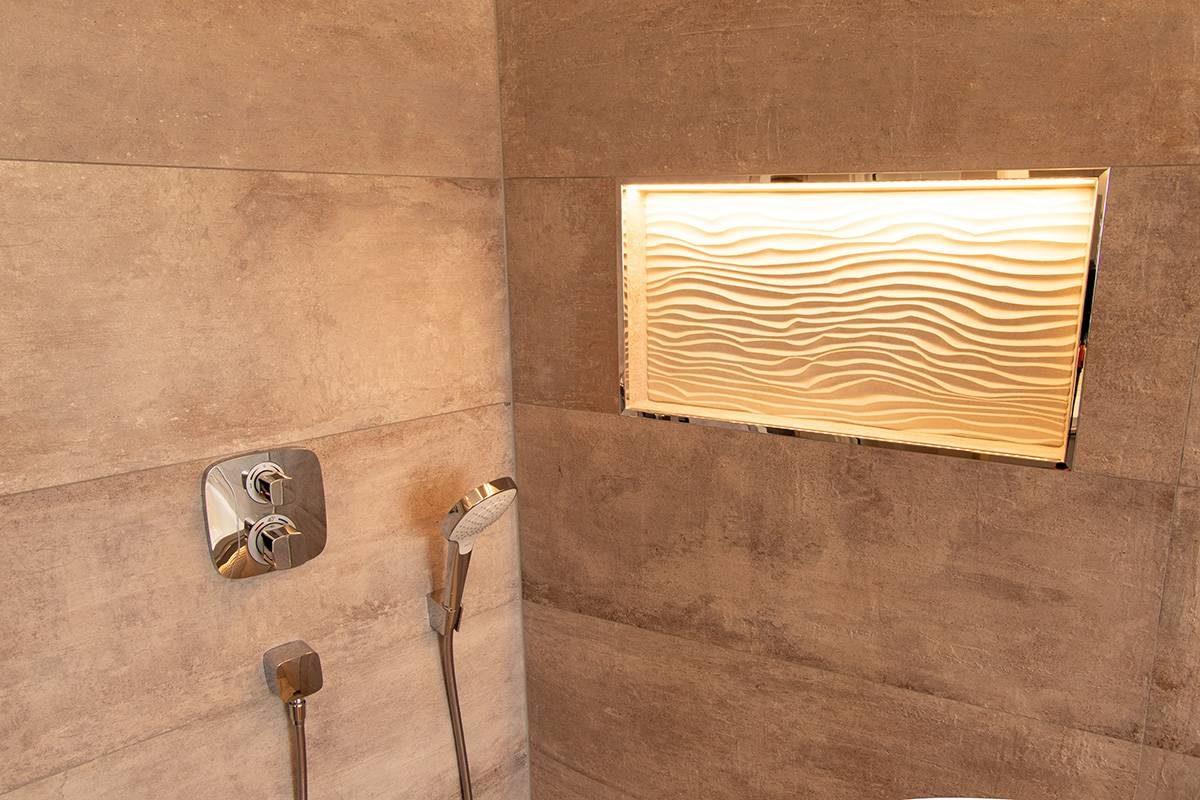 Abbildung Bad mit Glastrennwand Dusche mit grossformatigen Fliesen und Duschablage mit Beleuchtung