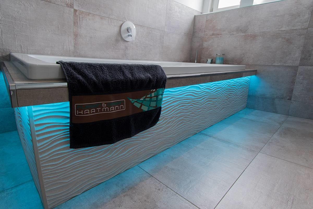 Abbildung Bad mit Glastrennwand Badewanne blau beleuchtet mit Handtuch