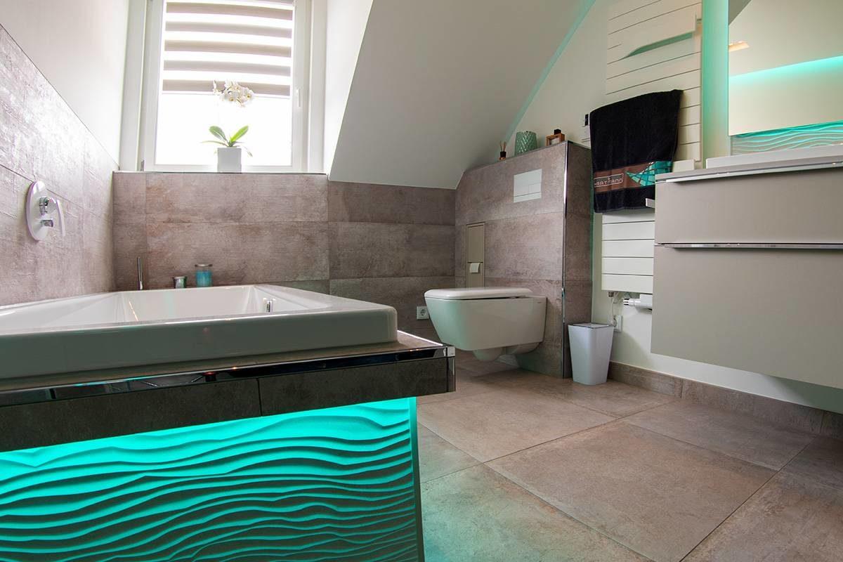 Abbildung Bad mit Glastrennwand Badewanne tuerkis beleuchtet und Blick auf Fenster, Toilette, Handtuchhalter und Waschbecken-Bereich