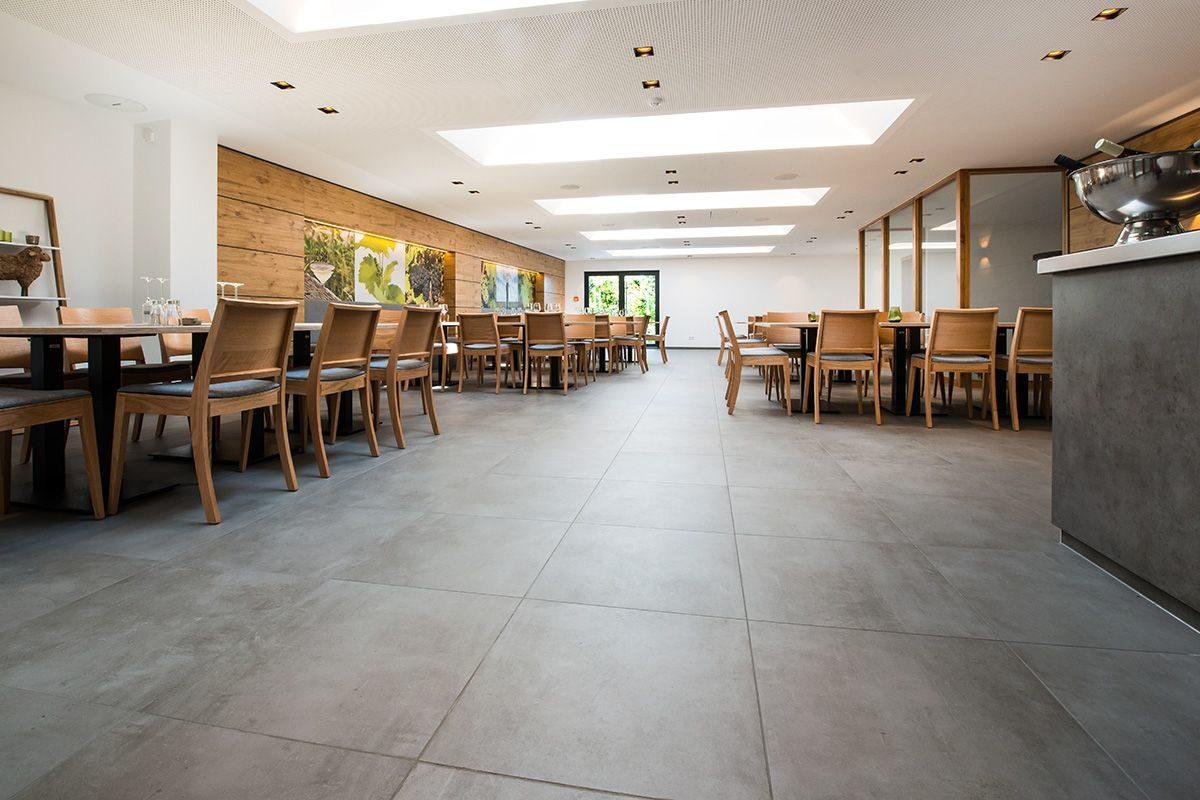 Veranstaltungsraum Weingut Lamm Jung graue Bodenfliesen dezente Einrichtung und indirekte Deckenbeleuchtung