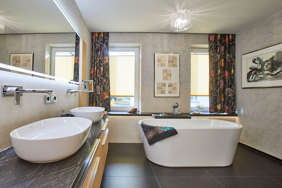 Traumbad mit Naturstein und großformatigen Fliesen Blick auf Doppelwaschbecken und frei stehende Badewanne mit dunklem Fliesenboden