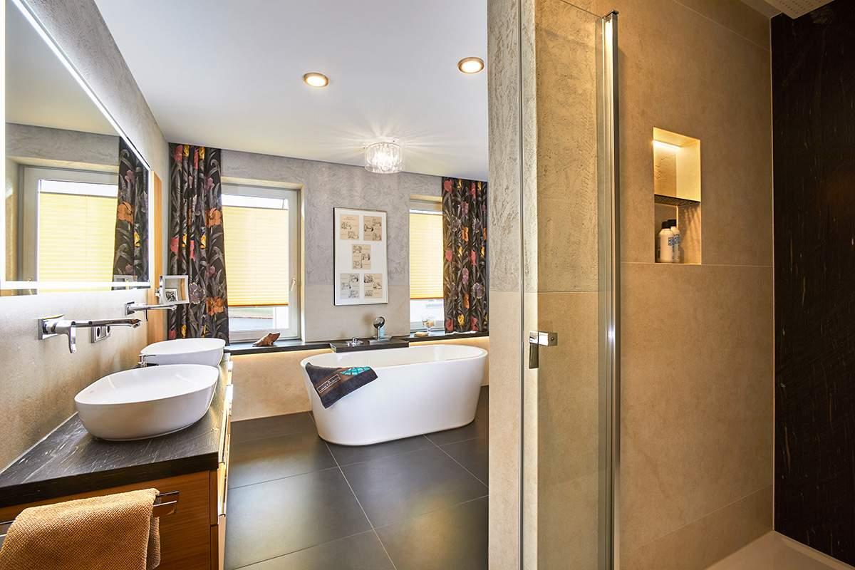 Traumbad mit Naturstein und großformatigen Fliesen Blick vom Duschbereich auf Doppelwaschbecken und freistehende Badewanne