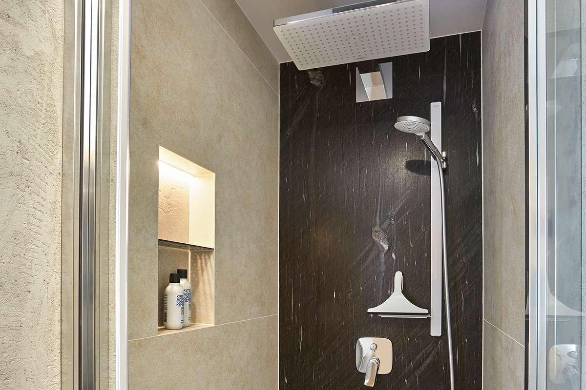 Traumbad mit Naturstein und großformatigen Fliesen Blick in Dusche mit Natursteinfliesen, mit Regendusche und praktischer Ablage in der Wand