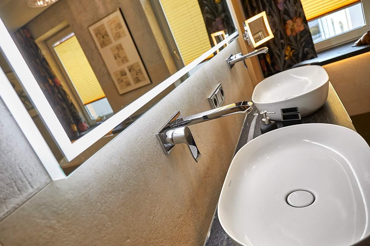 Traumbad mit Naturstein und großformatigen Fliesen modernes Doppelwaschbecken mit Wasserhähnen aus der Wand und beleuchtetem Spiegel