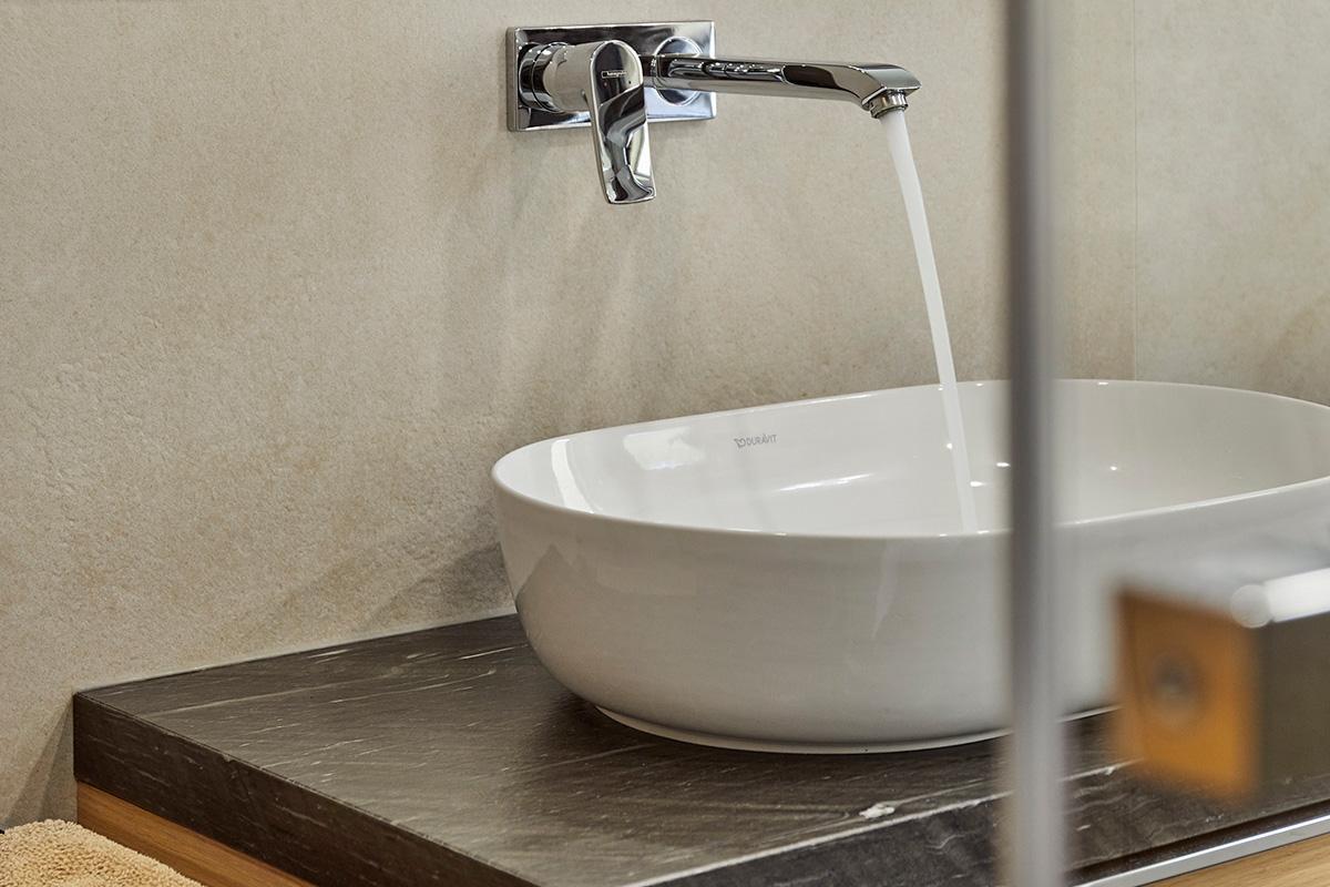 Traumbad mit Naturstein und großformatigen Fliesen Blick auf modernes Waschbecken mit laufendem Wasser aus dem Wasserhahn auf dunklem Naturstein