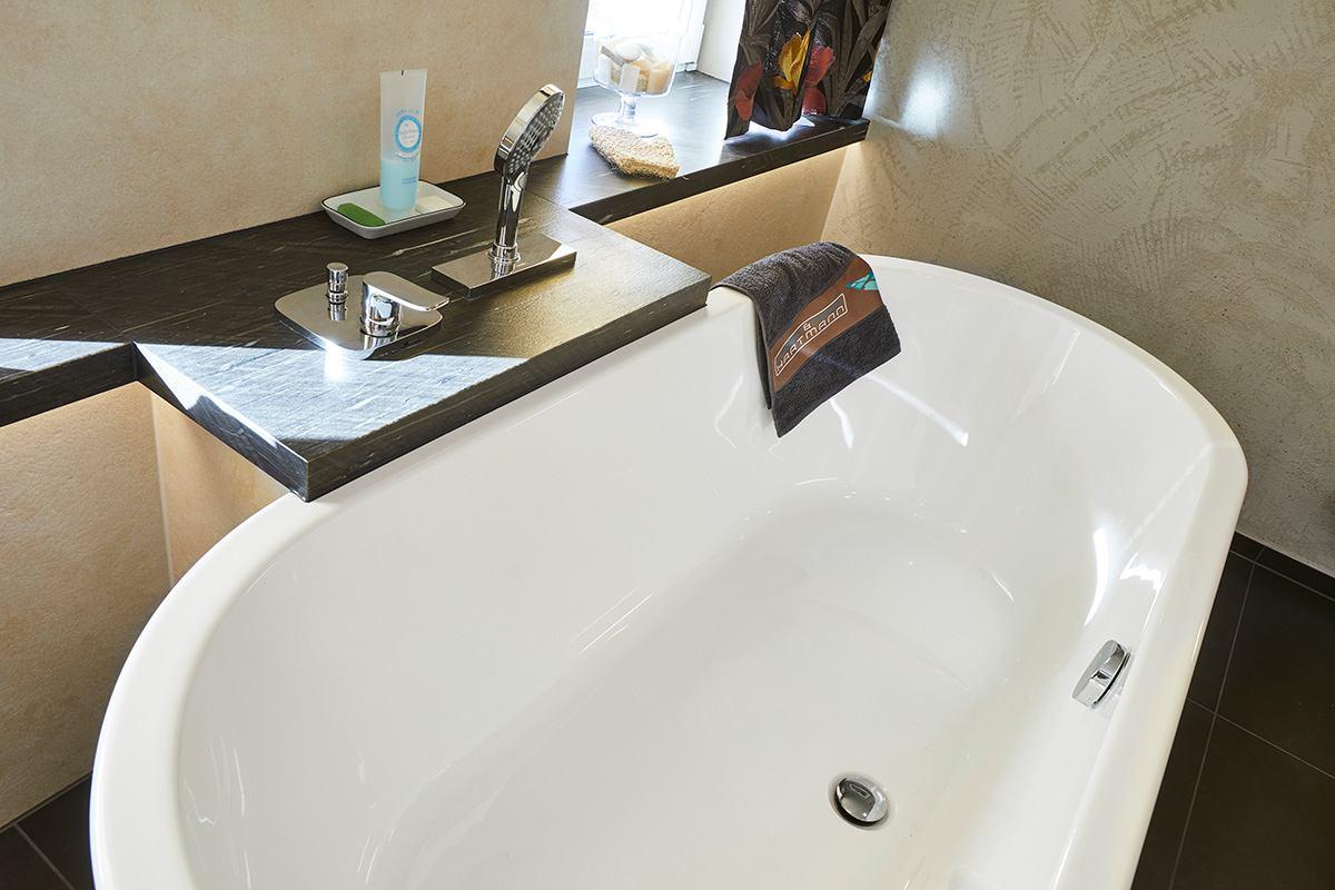 Traumbad mit Naturstein und großformatigen Fliesen Blick auf die freistehende Badewanne mit praktischer Ablage und in die Ablage integrierte Armaturen