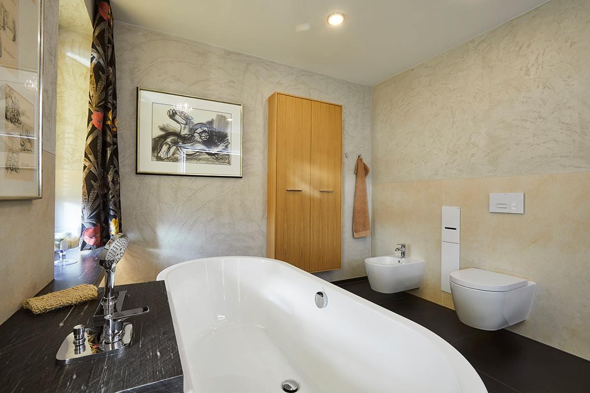 Traumbad mit Naturstein und großformatigen Fliesen Blick auf Badewanne, Sanitärkeramiken und Badschrank aus Holz