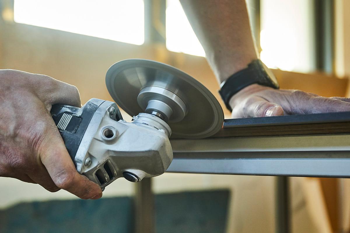 Schneiden einer Gehrungskante mit einem Winkelschleifer Detailaufnahme