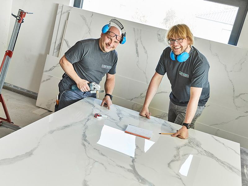 Abbildung Fliesenlegermeister Rene Hartmann mit Mitarbeiter bei der Bearbeitung von XXL-Fliesen