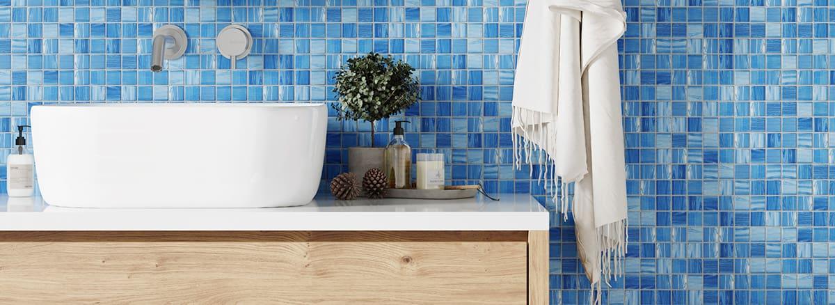 Blaue Mosaikfliesen mit weißem Waschbecken und Waschbeckenunterschrank aus Naturholz & Dekoration